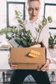 Fired businesswoman holding box