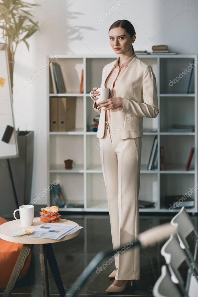 Young businesswoman holding cup