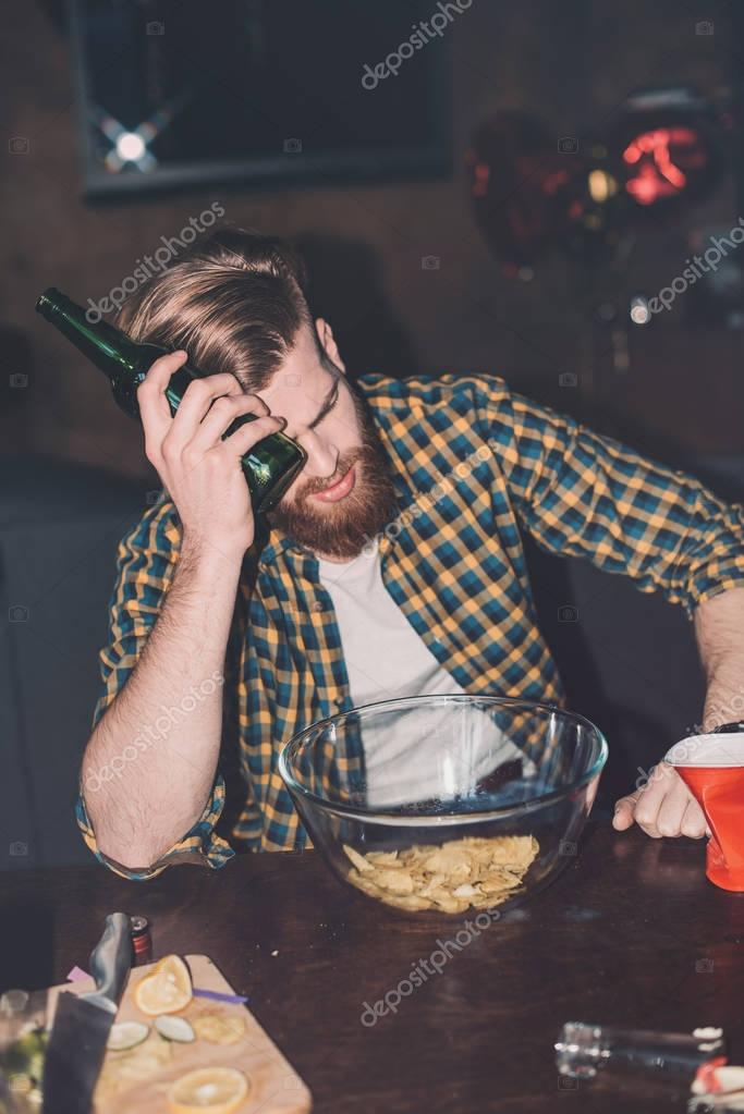 man with headache holding beer