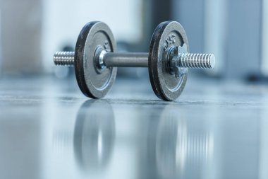 metallic dumbbell on floor