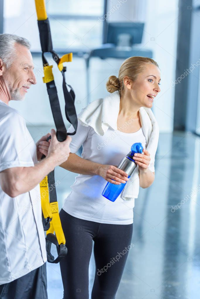 sportswoman and sportsman with resistance band