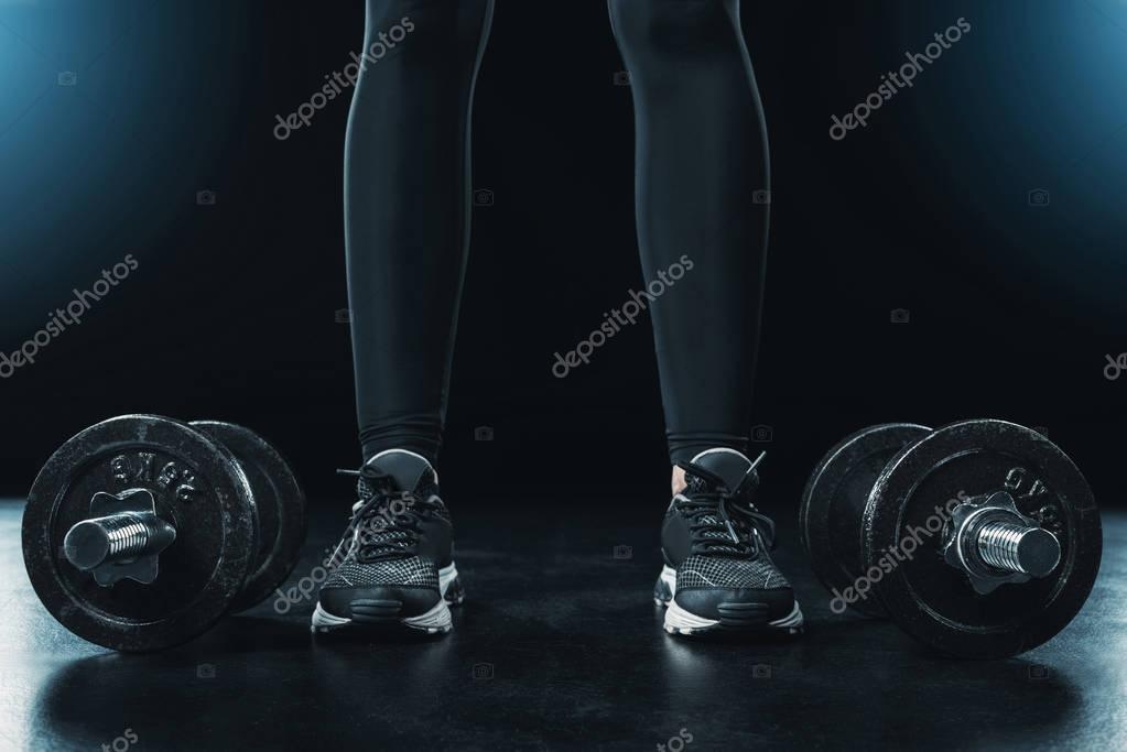sportswoman standing near dumbbells