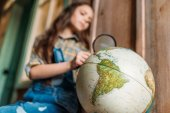 Fotografie girl with magnifying glass and globe