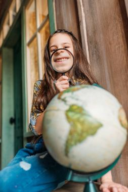 girl with magnifying glass and globe