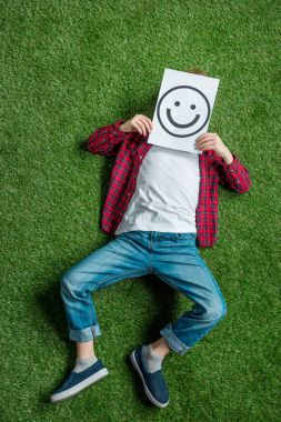 kid covering face with picture