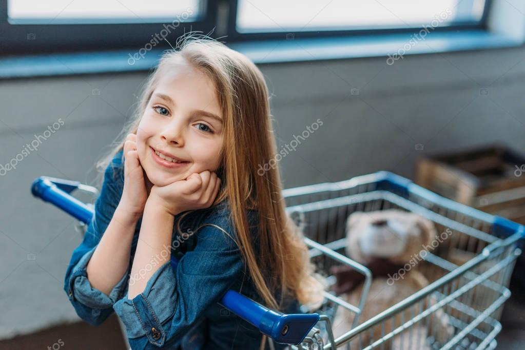 Girl sitting in shopping cart