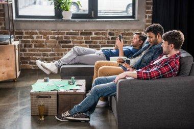 men relaxing on sofa
