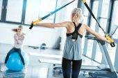 Fotografie Blonde Fitness Frau training mit Trx-Fitness-Riemen