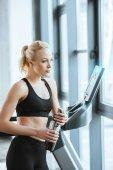Junge attraktive Frau ruht nach dem Training auf Laufband