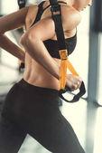 Blonde Fitness Frau training mit Trx-Fitness-Riemen