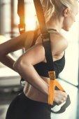 Žena blond fitness trénink s popruhy trx fitness