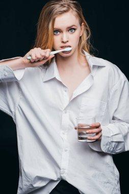 woman in male shirt brushing teeth