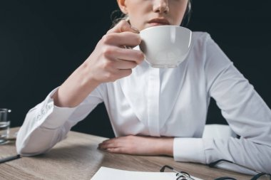 Woman sitting at table with cup of coffee