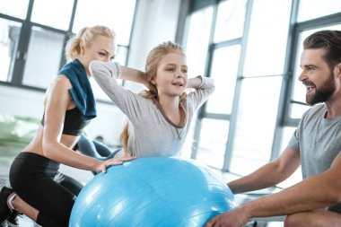 Cute gir exercising on swiss ball with parents