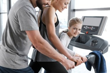 Happy family workout on treadmill, side view