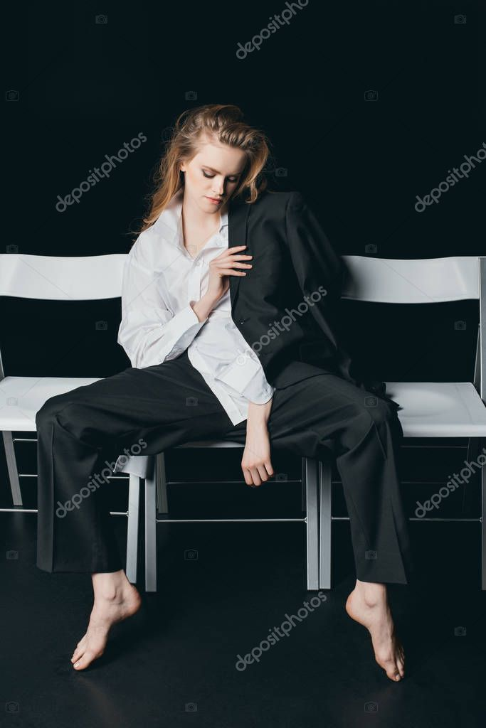 Woman in male shirt sitting on chairs
