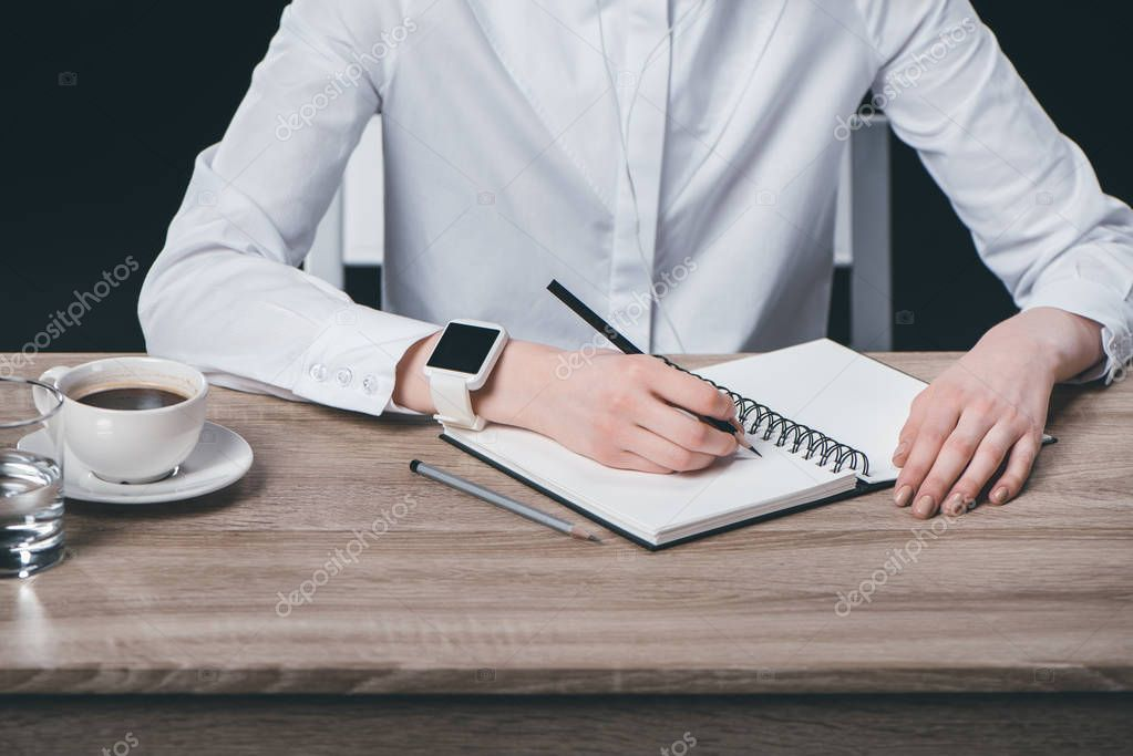 Woman sitting at table and making notes