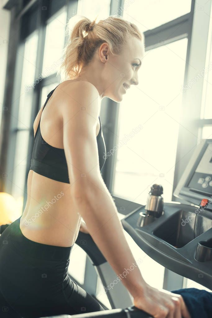 Blonde woman workout on treadmill, side view