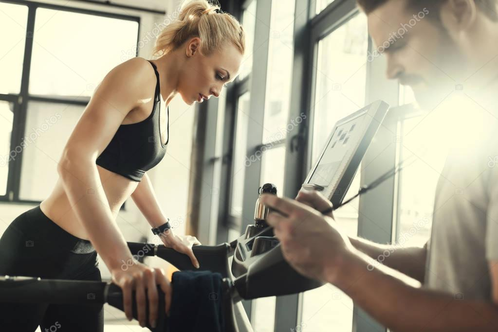 Blonde woman workout on treadmill and trainer with timer, side view