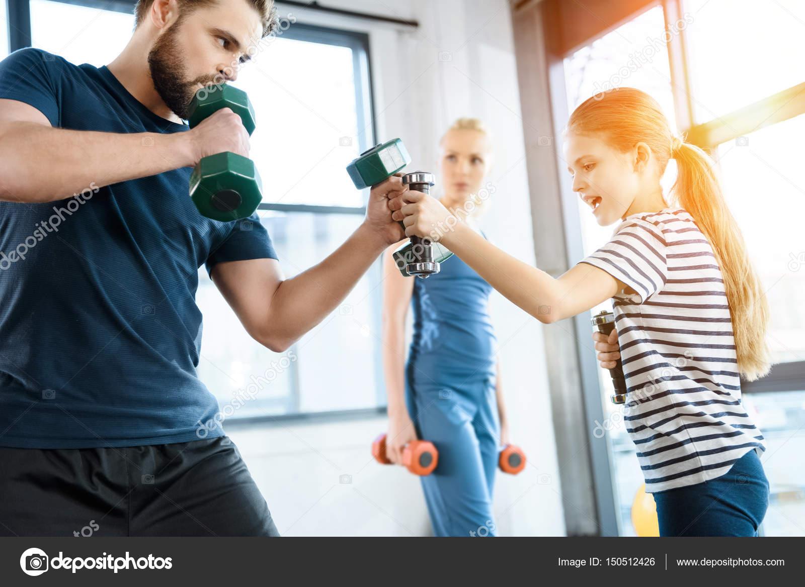 Ευτυχισμένη οικογένεια στην άσκηση με βάρη στο γυμναστήριο — Εικόνα από  ArturVerkhovetskiy bd6ef81a101