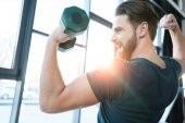 Photo Handsome young guy workout with dumbbell