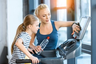 Woman trainer with small girl workout on treadmill