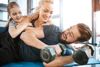 Happy family having fun at gym, man holding dumbbells