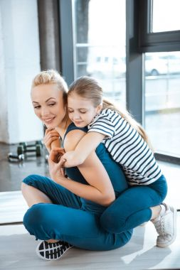 Cute girl embrace mother at fitness club