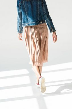 woman in beige skirt and denim jacket