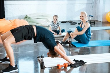 People doing gymnastics, man performing bridge pose at fitness studio