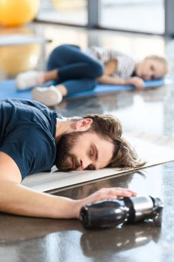 tired sleeping man lying on mat at gym