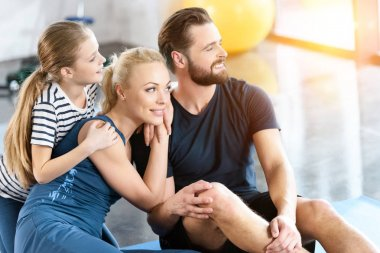 Portrait of happy family sitting at gym