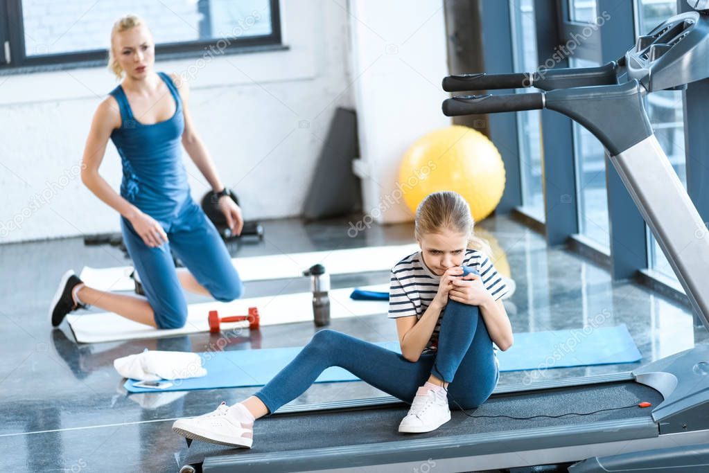 girl injured knee sitting on treadmill