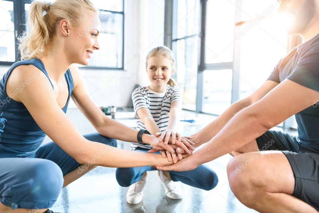 Family holding hands together at fitness center