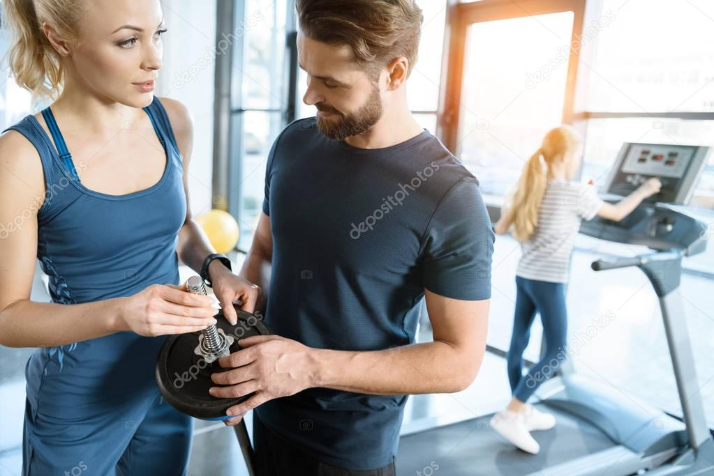 Young man and woman standing with barbell while small girl workout on on treadmill at gym