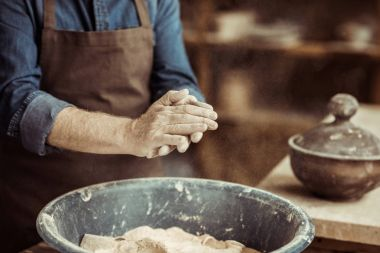 Close up of male potter hands taking clay from a bowl