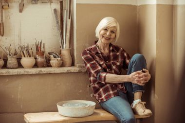 Happy senior woman sitting on bench near wall at workshop