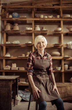 Front view of senior woman sitting on chair against shelves with pottery goods