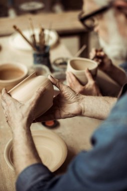 Close up of senior potter in apron and eyeglasses examining ceramic bowl