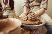 Fotografie Close up of child hands working on pottery wheel at workshop
