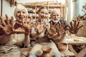 Grandmother and grandfather with granddaughter showing hands in clay in workshop