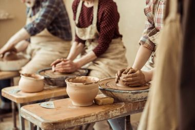 Cropped image of grandmother and grandfather with granddaughter making pottery at workshop