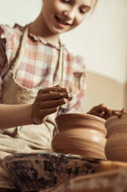 Close up of little girl making pottery on wheel at workshop