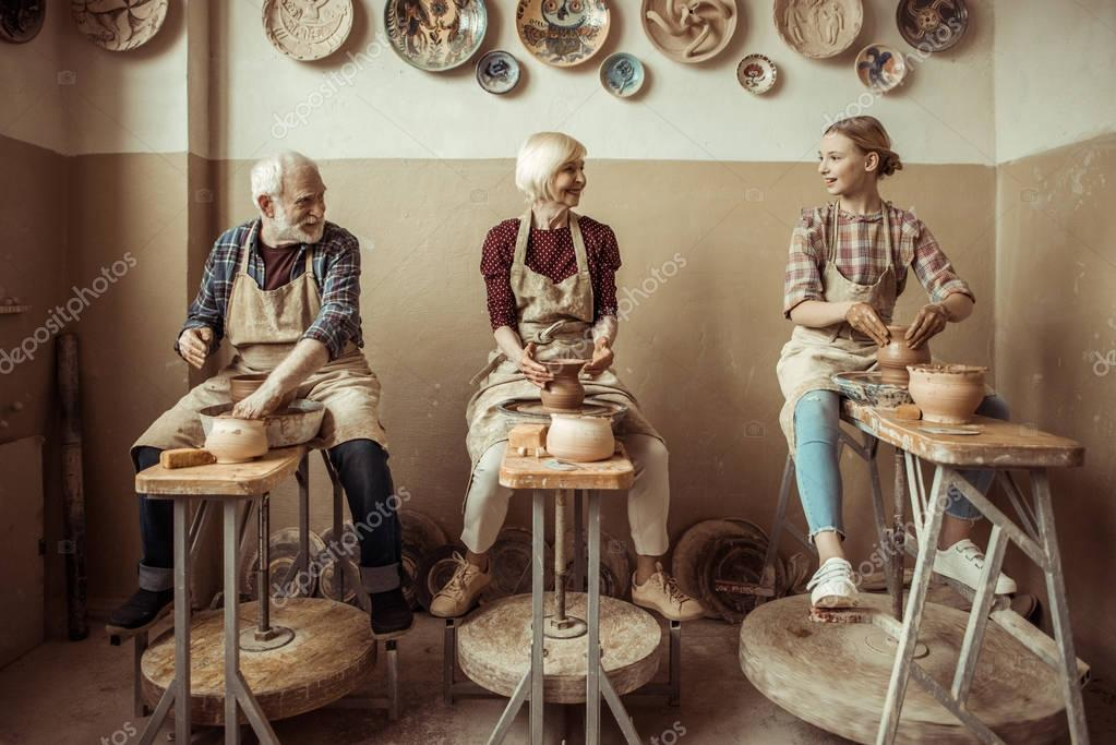 Grandmother and grandfather with granddaughter making pottery at workshop