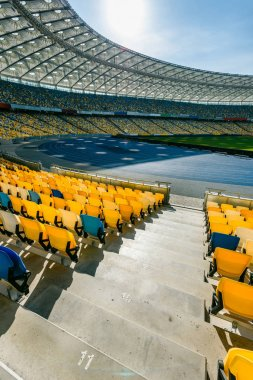 Rows of yellow and blue stadium seats  on olympic stadium stock vector