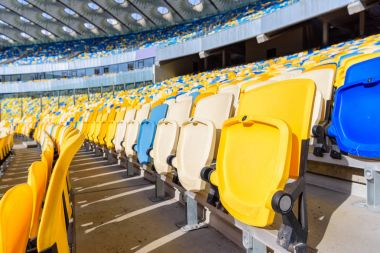 Rows of yellow and blue stadium seats on soccer stadium stock vector
