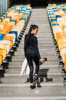 tired sportswoman on stadium seats