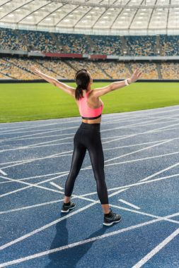 Sportswoman exercising on stadium