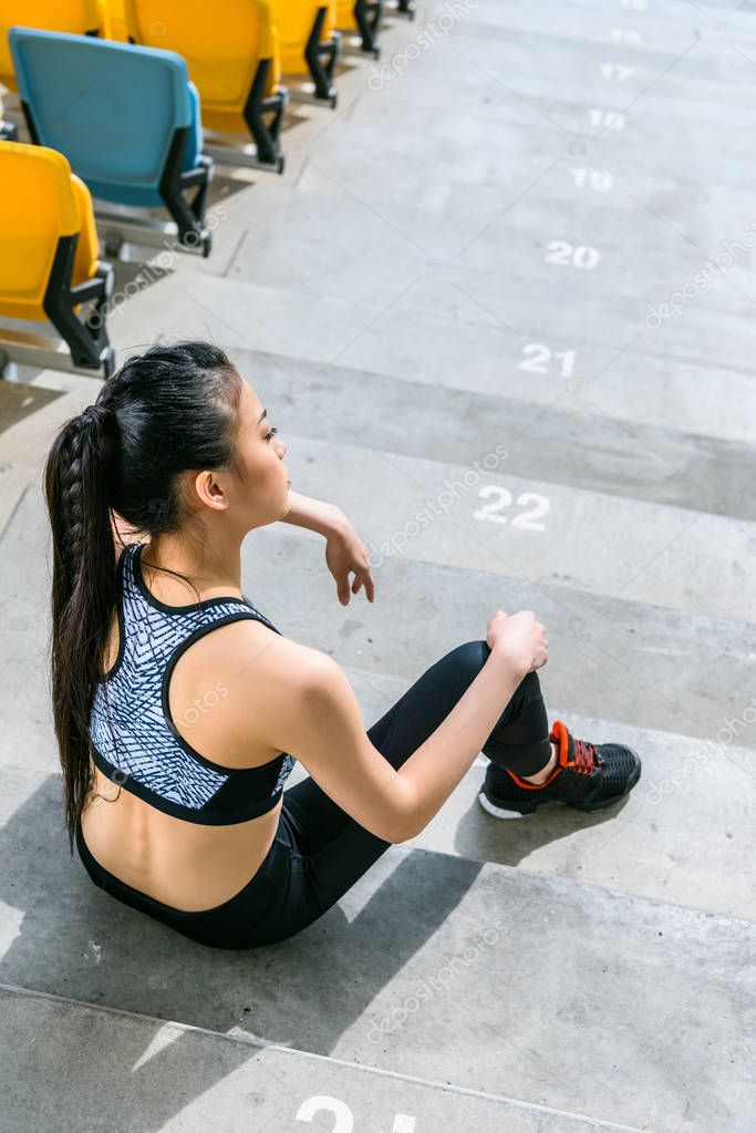 tired sportswoman sitting on stairs