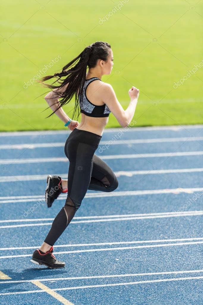 sportswoman training on running track